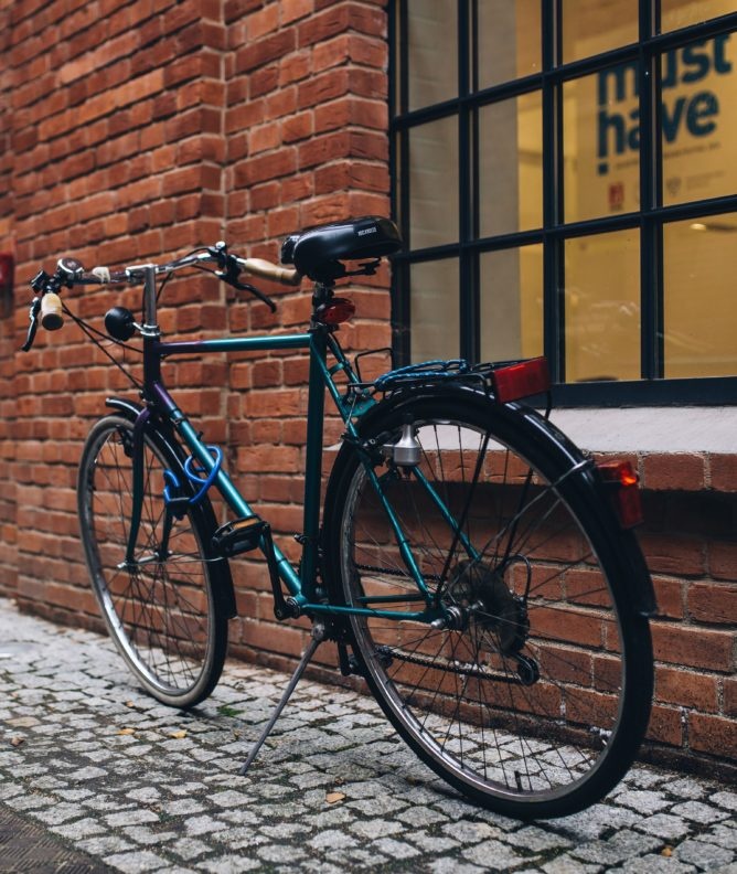 Bicycle parked in front of a brick wall