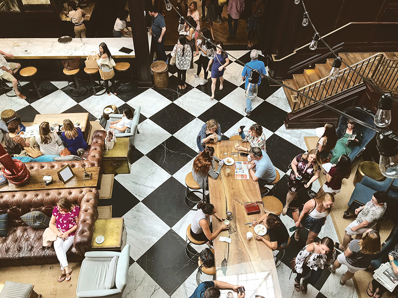 Overhead photo of people eating, drinking, and working at community tables at the Oxford Exchange in Tampa, Florida